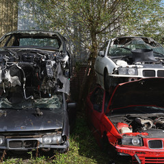 Wrecked cars stacked on top of eachother at a scrapyard