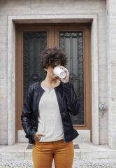 Portrait of young woman drinking coffee outdoors.