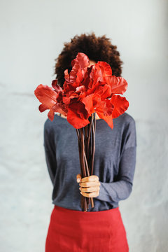 Woman covering her face with a bouquet of red flowers.