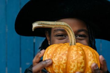 Smiling black girl holding a pumpkin