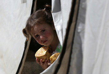 An Internally displaced child holds a pomegranate as she looks out from a tent at a camp in the town of Soussian in Aleppo countryside