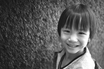 Black and white portrait of a cute, adorable, young kid looking at camera