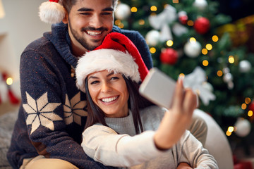 Couple in love having fun and take pictures of Christmas on mobile phone .