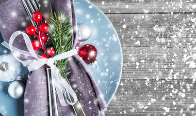 Christmas dinner plate decoration with xmas ornaments on old wood background. Merry christmas card. Winter holiday theme. Happy New Year. Glitter snow effect