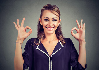 Cute playful young woman showing two ok signs over gray background
