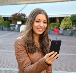 Smiling hipster girl is reading pleasant text message from her friend on mobile phone outdoor.
