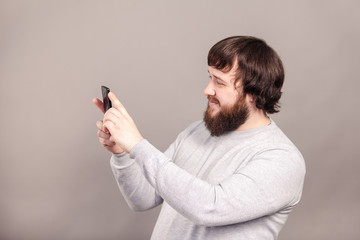 Side view of young handsome man wearing light gray shirt taking photo with mobile phone isolated over dark studio background.