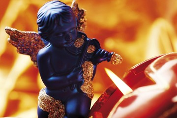 Christmas decoration, gold winged blue angle cherub playing the violin next to a candle