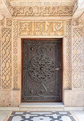 Closed wooden aged door with ornate bronzed floral patterns at the mosque of The Manial Palace of Prince Mohammed Ali Tewfik, Cairo, Egypt