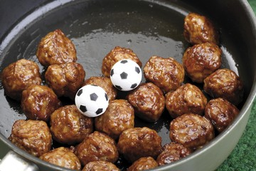 Football fast food - meatballs in a pan with two miniature footballs