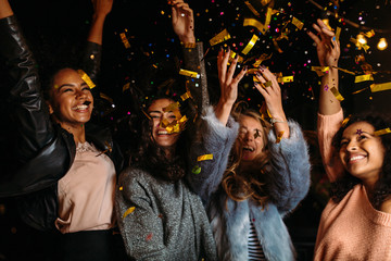 Female friends raised hands up, enjoying party outdoors