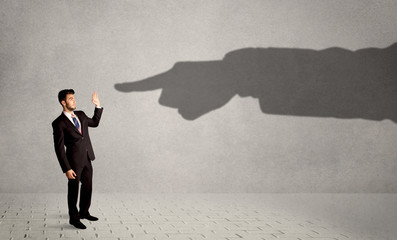 Business person looking at huge shadow hand pointing at him concept