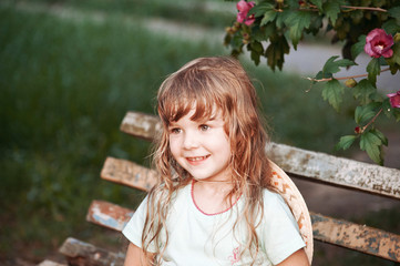 Portrait of a little girl. The girl is sitting on an old bench. Bush with pink flowers.
