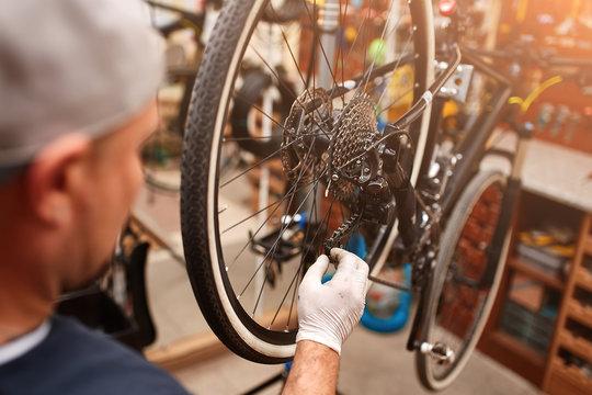 Mechanic repairing bicycle in his workshop