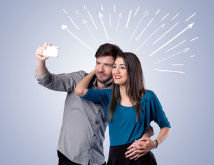 Cute couple taking selfie with arrows