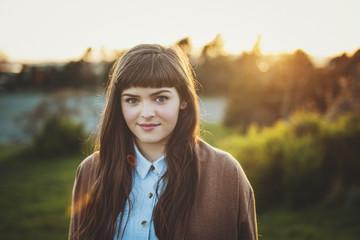 Beautiful teen girl enjoying nature at sunset