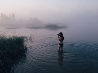 Woman in the lake with camera