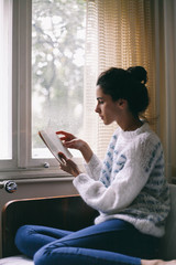 Beautiful woman reading a book in her room near the window
