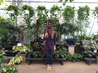 A woman stands in a greenhouse surrounded by plants.