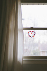 A serene image of a window with a heart ornament.