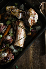 Crop view of a tray of roasted oxtail and beef bones with vegetables.