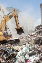 An excavator clearing off debris of a fallen building.