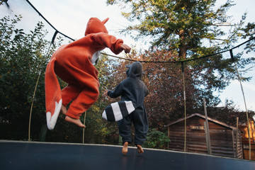 Cute girl in fox and boy in raccoon costume jumping on trampoline