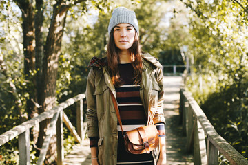 Young hipster woman standing in a wooden bridge in the forest.