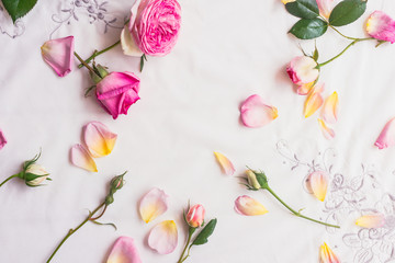 background roses scattered on a vintage embroidered linen tablecloth