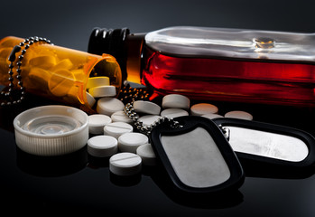 Veterans returning with PTSD and self medication with prescription pills and alcohol concept with a dark themed image of military dog tags surrounded by a prescription bottle and a flask of liquor