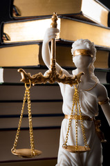 Legal code, enforcement of the law and blind Iustitia concept with statue of the blindfolded lady justice ( Dike in Greek and Justitia in Roman mythology), and a stack of books