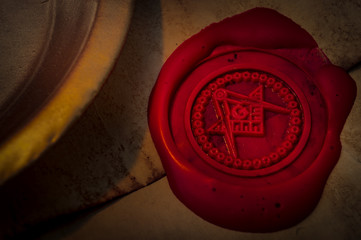 Freemason secret symbol concept with vintage letter under a candle, sealed with red wax seal with the square, the compass and the G letter in the middle, one of the most identifiable masonic symbols