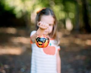 Cute young girl holding up a halloween pumpkin