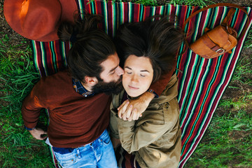 Man kissing his girlfriend resting on a striped blanket.