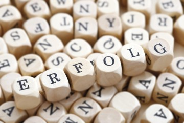 Erfolg, German for success, written with wooden letters