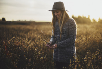 Young Blonde Woman Picking Flowers in Field