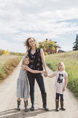 Modern family standing on rural road