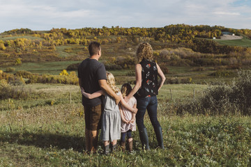 Modern family standing together against autumn landscape