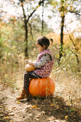 Cut baby girl with pumpkins on autumn