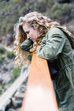 Side view of contemplative teen girl with long curly hair