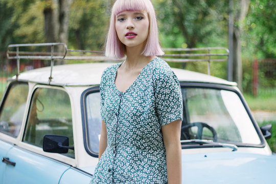 Portrait of a beautiful young woman near oldtimer car