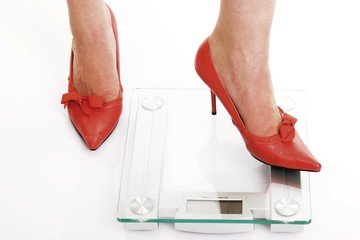 Woman wearing red high heels getting onto the scale