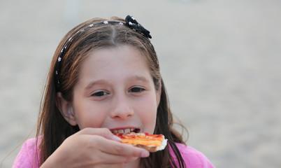 caucasian little girl eats pizza on the beach