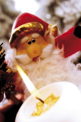 Burning white candle in front of Father Christmas figurine decoration