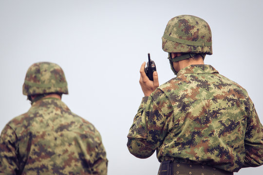 Soldiers in action communicating on walkie talkie