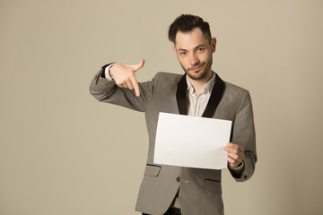 a young man in a suit with an unshaven face with white paper with an announcement in his hands