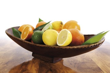 Citrus fruits in brown wooden bowl