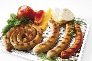 Aluminium barbecue tray with bratwurst, bratwurst snail, beef bratwurst, grilled tomato, capsicum, herbs and white bread