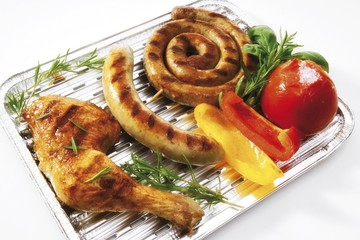 Aluminum barbecue tray with bratwurst, bratwurst snail, chicken drumstick, grilled tomato, capsicum and herbs