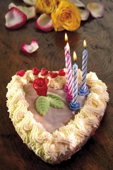 Small candles on a heart-shaped cake